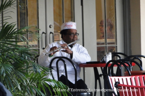 Staff member of Morning Call Coffee Stand playing the flute during break, City Park, New Orleans