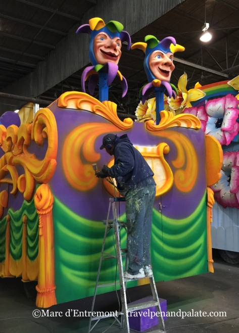 spray painting a prop at Mardi Gras World