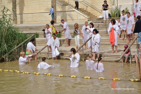 Present day Christian baptisms, right bank Jordan River (Israel).The site at which John the Baptist baptized Jesus of Nazareth is shared by Jordan and Israel but divided in half.